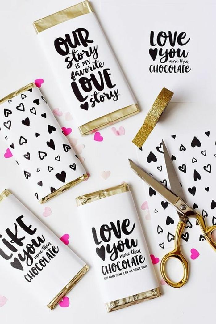 ideas para san valentin, regalo romántico conchocolates envueltos en papel con mensajes de amor, blanco, negro y dorado