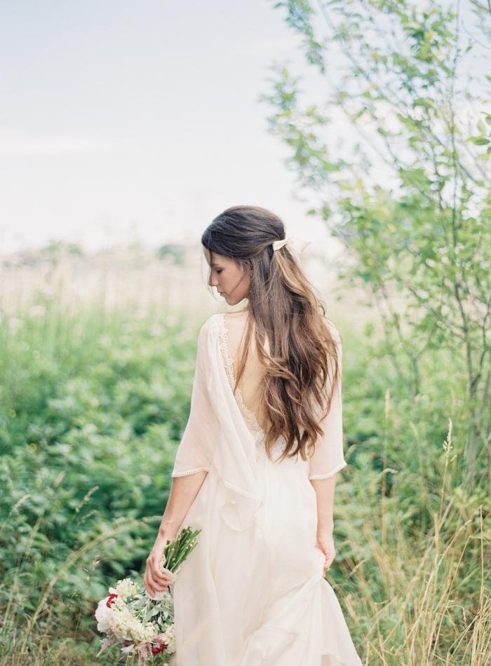 peinados semirecogidos, mujer vestida de novia con ramo de flores, pelo castaño largo. semirecogido romántico con broche