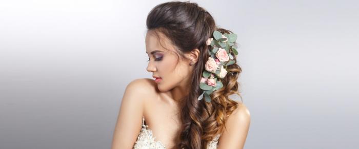 semirecogidos pelo rizado, mujer de perfil, peinado de lado para novia, semirecogido con trenza cola de pez y decoración con rosas