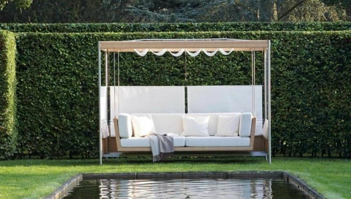 jardines modernos, tendencias 2018, bonito seto vivo alto y lago grande, pérgola moderna con sofá tipo cuña en beige y blanco