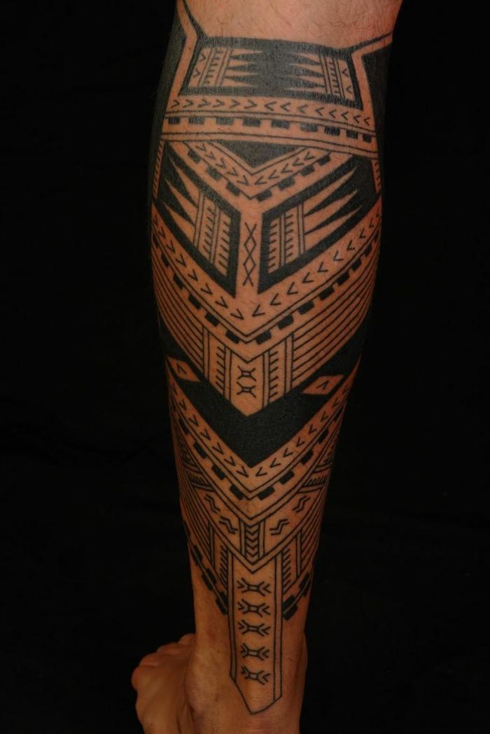 tatuajes antebrazo, pierna de hombre tatuada parte inferios, tatuaje con motivos polinesios y zonas en negro