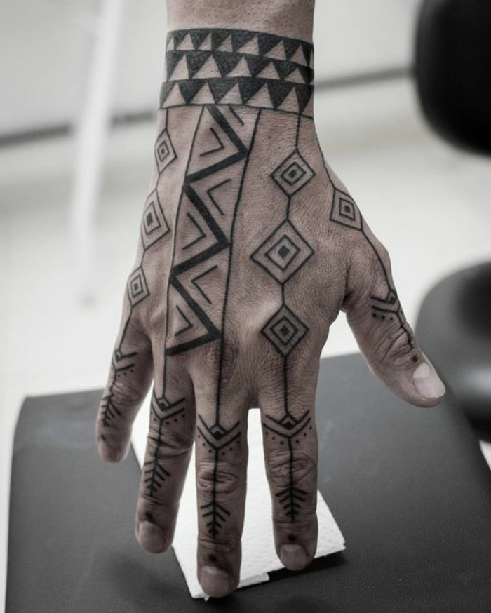 tatuajes antebrazo, tatuaje maorie en la mano y los dedos, figura geométricas, brazelete con motivo dientes de tiburón