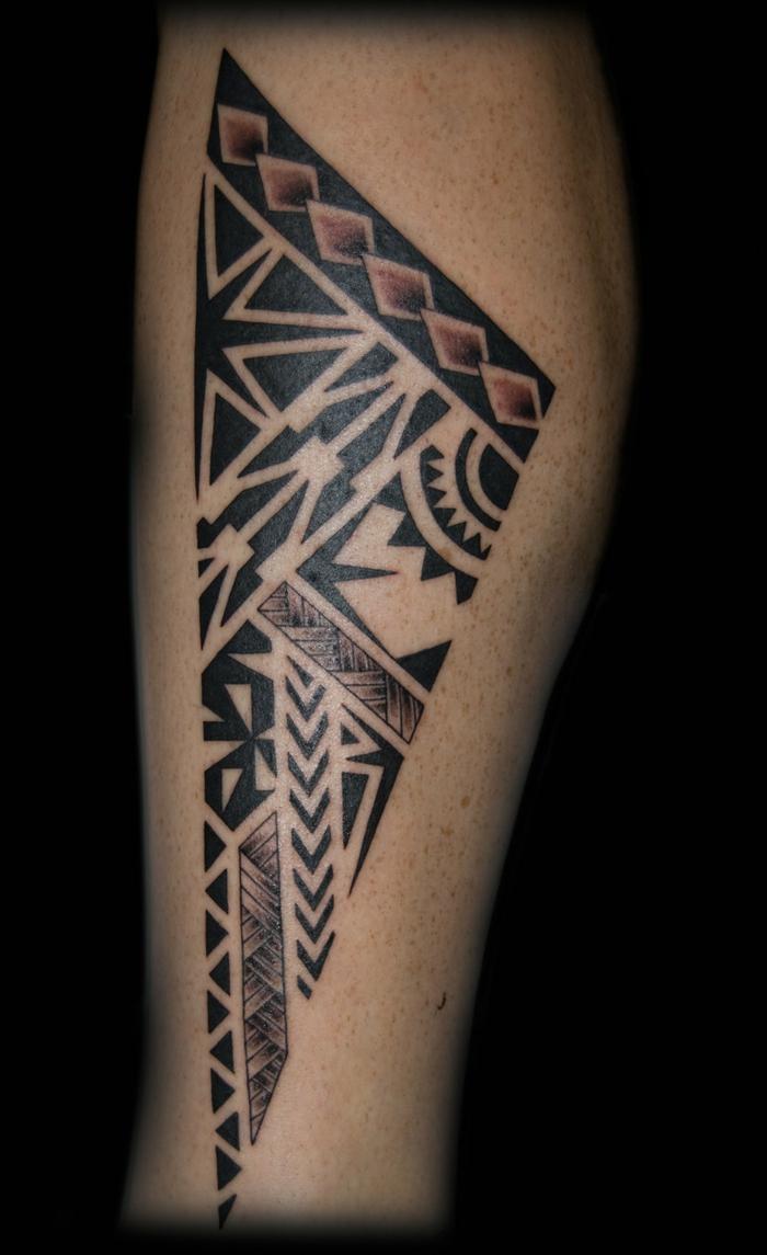tatuajes antebrazo, tatuaje con motivos maori en pierna inferior de hombre, punta de lanza estilizada