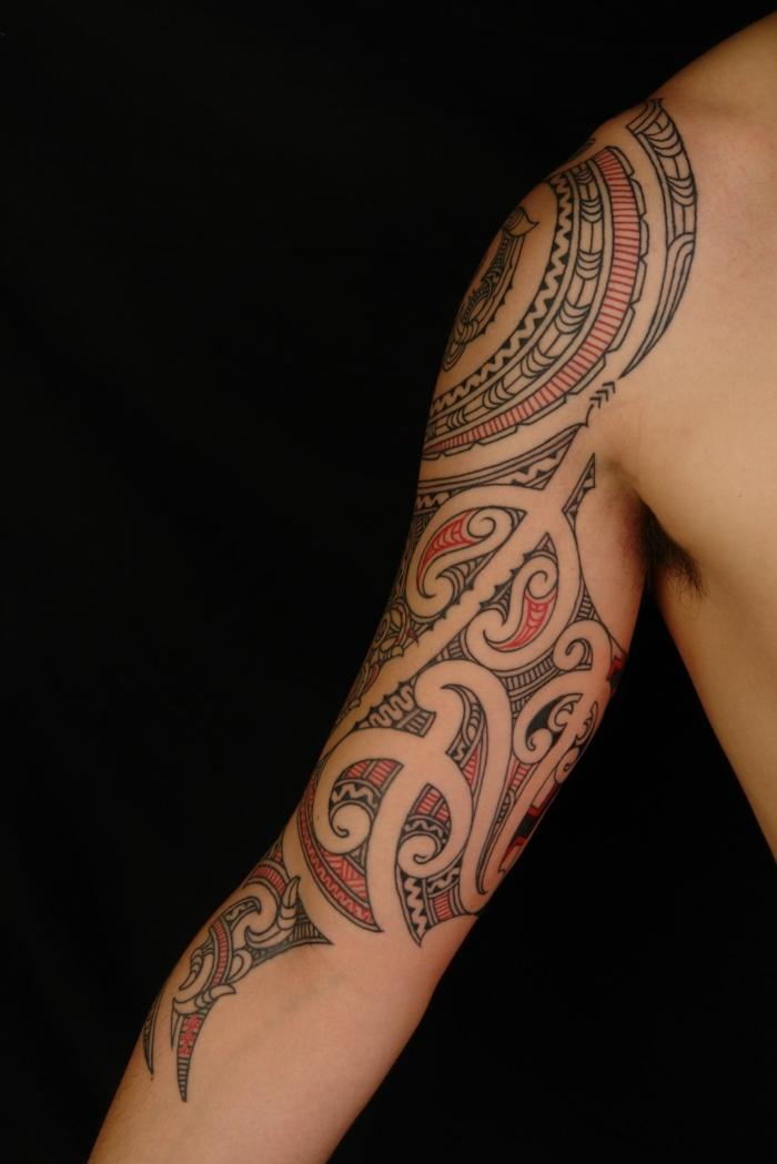 tatuaje maori, brazo de hombre tatuado en negro y rojo, motivos polinesios, figuras geométricas