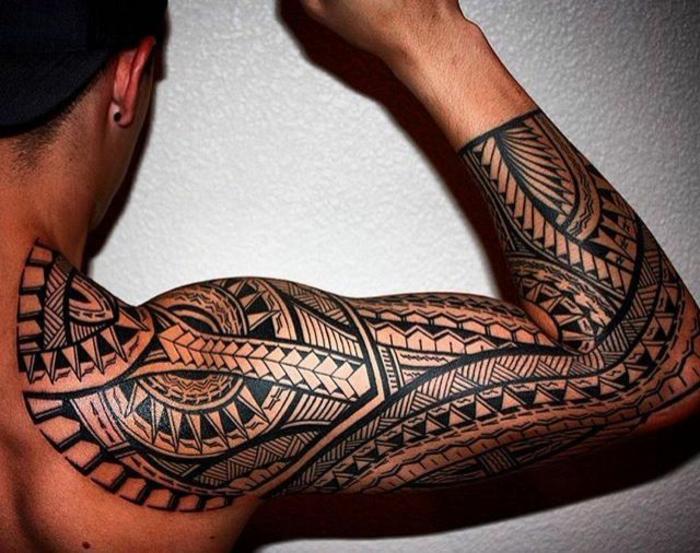 tatuaje brazo, tatuaje con símbolos polinesios en brazo y hombro, hombre con brazo levantado, dientes de tiburón y punta de flecha