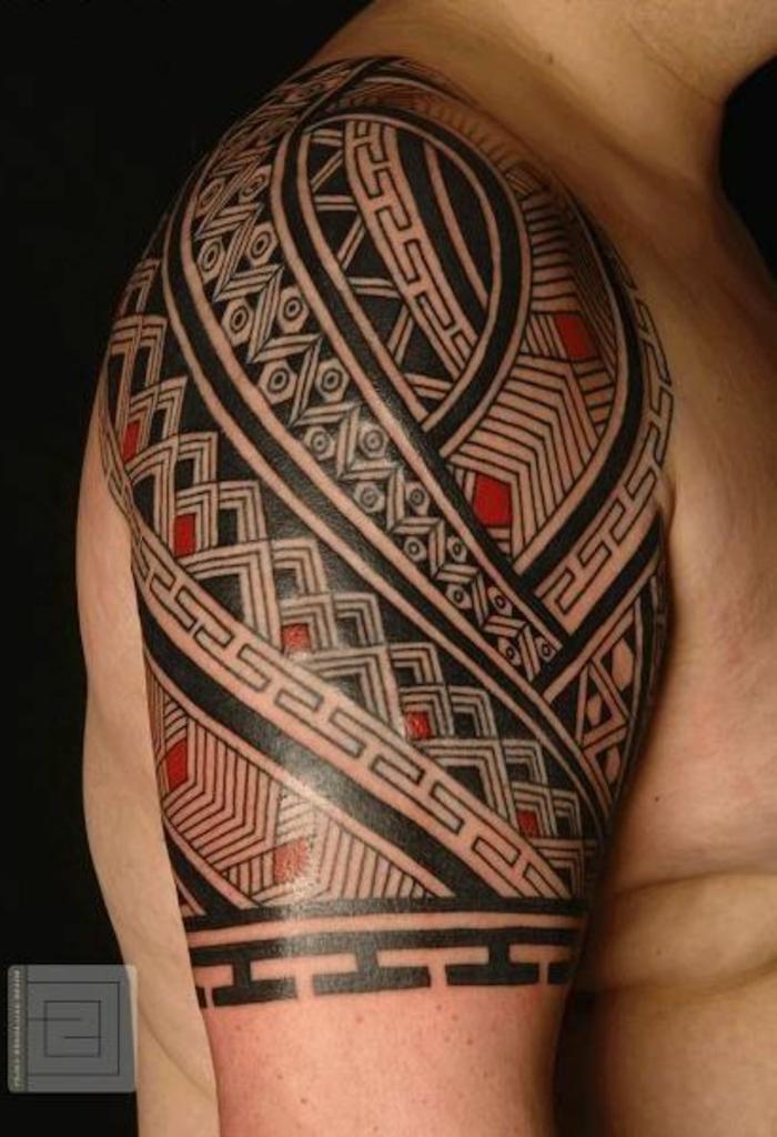 tatuajes brazo, tatuaje maori para hombre en rojo y negro en hombro y brazo, motivos maories dientes tiburrón