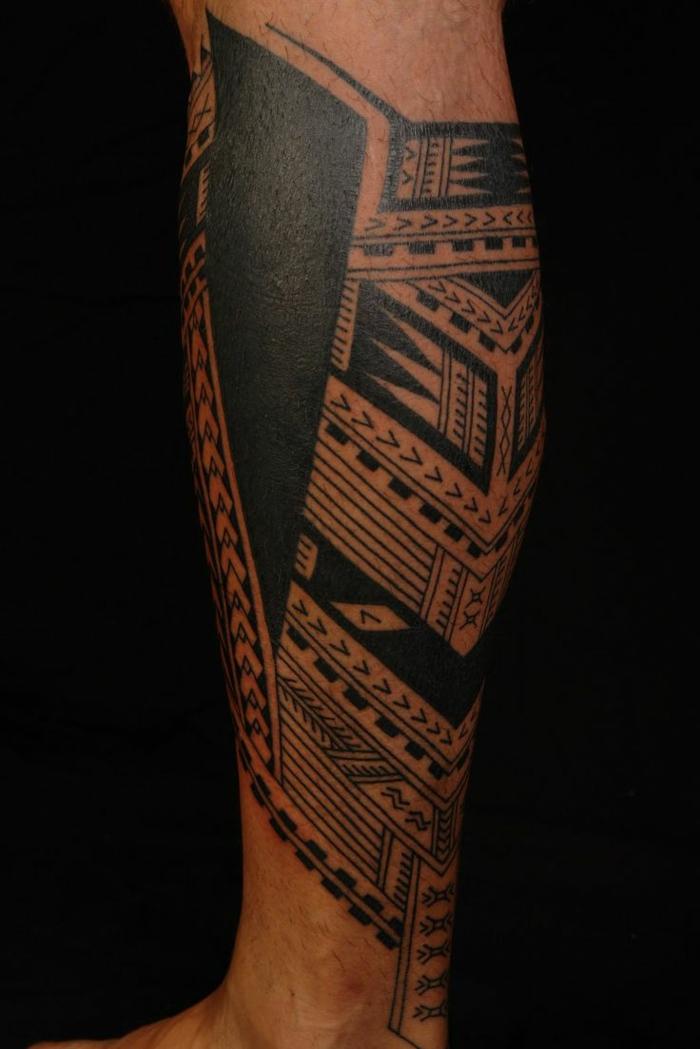 brazalete maori, pierna inferior de hombre con tatuaje polinesio, triángulo en negro sólido