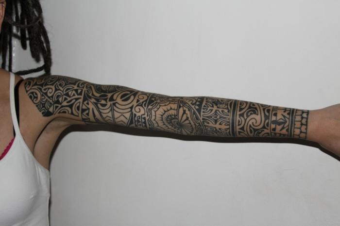 brazalete maori, mujer con rastas y blusa blanca, brazo entero tatuado, tatuaje maori con ojos de Tiki