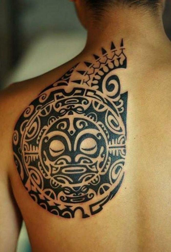 brazalete maori, tatuaje maori en espalda de hombre, motivos maories cabeza Tiki y oceano