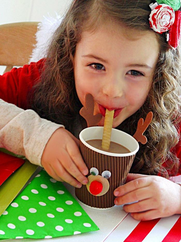como hacer adornos de navidad, niña con taza de café de cartón adornada como un ciervo, motivos navideños DIY