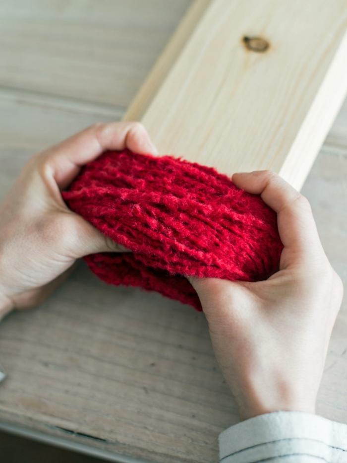 manualidades de navidad para niños, pasos para elaborar un pompón de hilo rojo, ideas originales para los niños