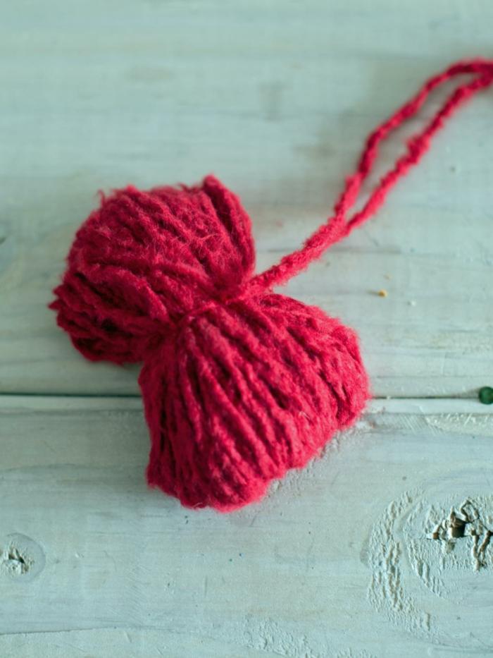 manualidades de navidad para niños, pequeño mono hecho de hilo para hacer un pompón decorativo para Navidad