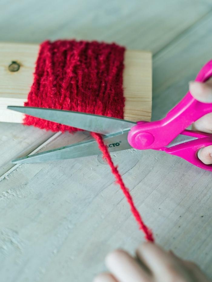 manualidades de navidad para niños, pasos para hacer un pompón rojo de hilo, enrollar en hilo a un trozo de madera
