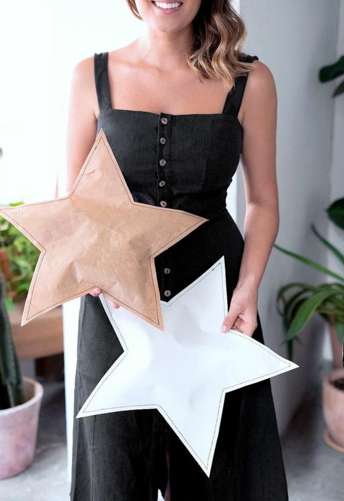 estrella de navidad, paquete de papel en forma de estrella, mujer con dos regalos empaquetados de manera original, estrellas de papel navideñas