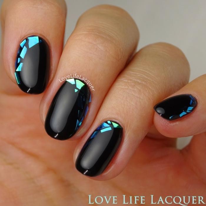 uñas pintadas, ejemplo de uñas de media longitud pintadas en negro con brillo y decoradas de partículas brillantes en tonos azules