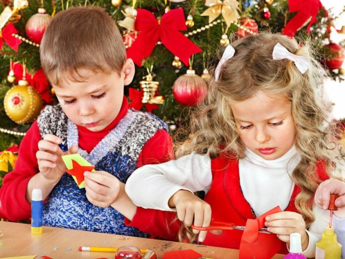 manualidades de navidad para niños, niño y niña al lado del árbol navideño, ideas para adornos navideños hechos a mano