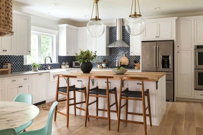 cocina americana, cocina con barra amueblada en madera, barra en blanco con encimera de madera y sillas con asientos negros, lámparas grandes de virdio