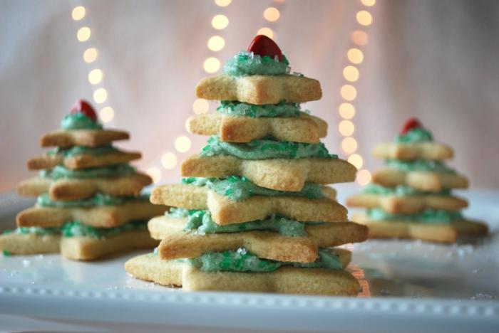 estrellas de navidad, galletas de mantequilla navideñas en forma de estrellas colocados en forma de árbol navideño, betún verde