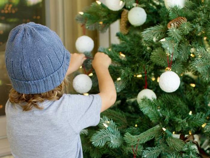 adornos navideños caseros, pequeño niño adornando el árbol navideño, bolas de poliestireno decoradas en blanco