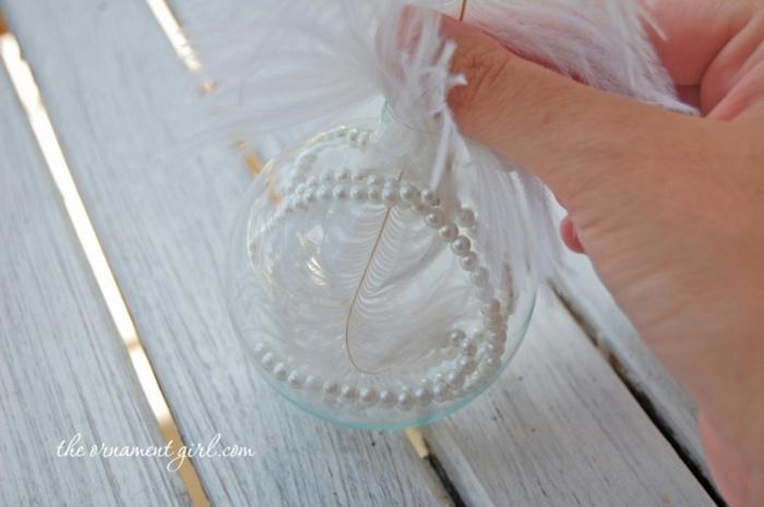 bolas navidad, instrucciones para hacer un ornamento navideño de una bola de cristal, perlas blancas y plumas decorativas