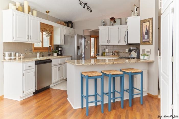 cocina americana, cocina en blanco con barra puesta en diagonal y sillas de barra con patas azules, suelo de parquet