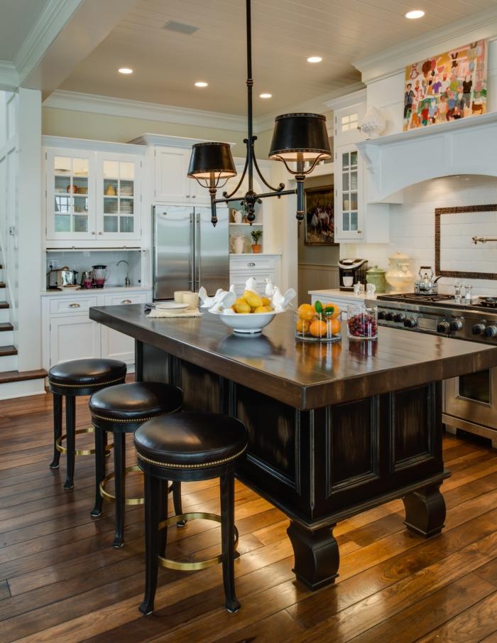 cocina americana, precioso ejemplo de cocina de madera en tonos oscuros, barra vintage y sillas tapizadas con piel, paredes y armarios blancos