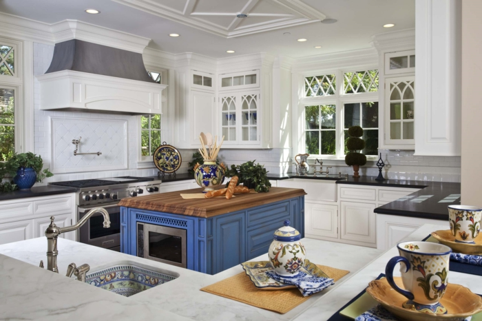 cocina americana, cocina en blanco con detalles en azul, barra en el centro del ambiente en azul con encimera de madera, cocina con muchas ventanas