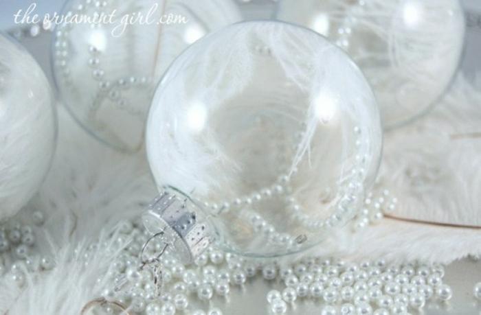 como hacer bolas de navidad, esferas de vidrio transparentes llenas de perlas blancas y plumas decorativas en blanco