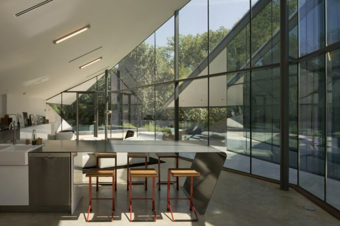 comedores, ejemplo contemporáneo de cocina con isla que sirve de comedor, espacio con techo inclinado y altos ventanales, isla moderna con sillas de barra