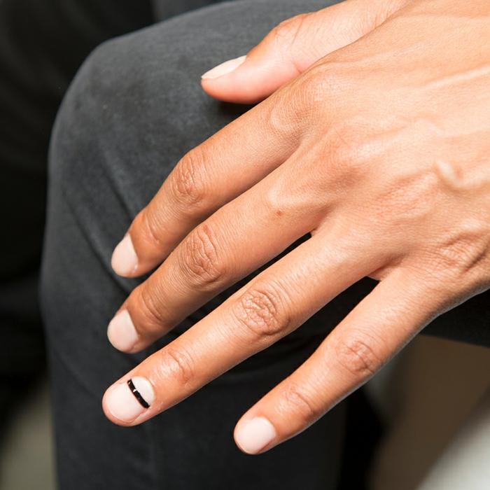 diseño de uñas, detalle pequeño en la uña anular, uñas cortas sin esmalte y pequeña raya horizontal en negro en el dedo anular