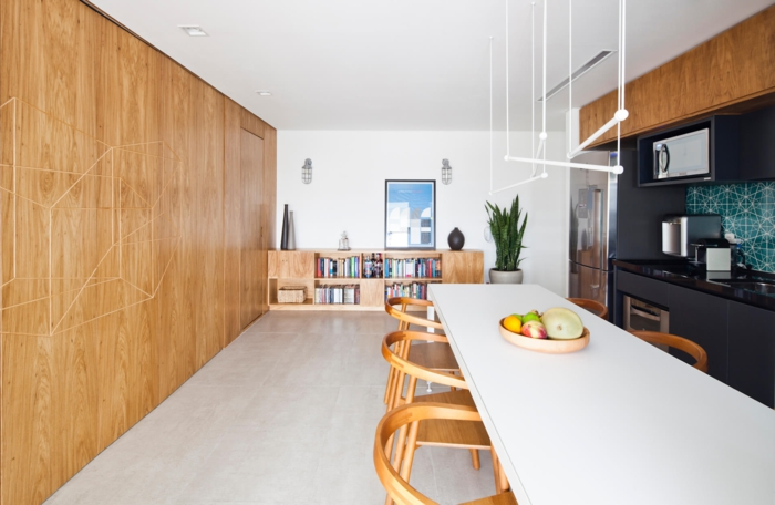 cocina americana, cocina espaciosa alargada con pared de madera clara, grande encimera blanca con sillas de madera, lámparas modernas colgantes, rincón pintado en negro