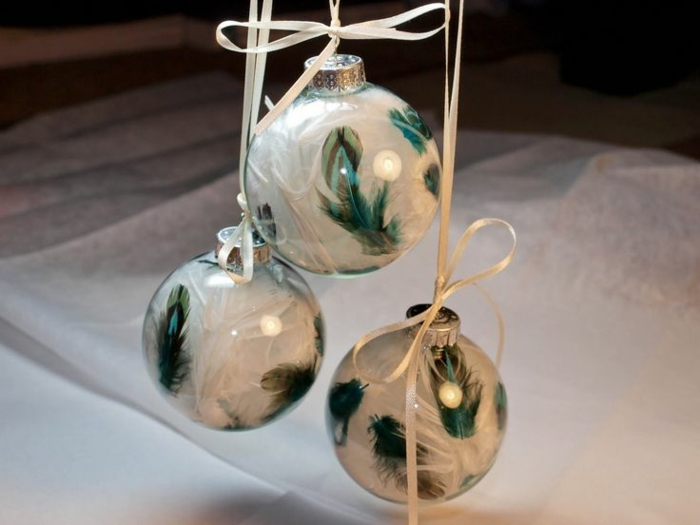 decoracion navideña casera, tres bolas de cristal transparentes llenas de plumas blancas y verdes, bonitos elementos para el árbol navideño