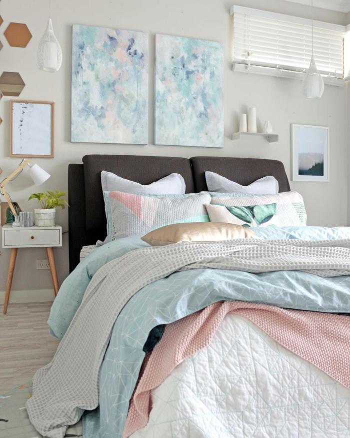 dormitorio de matrimonio, bonita combinación de colores pastel, paredes en gris suave, cobijas en azul y rosa, cuadros modernistas que dan un toque elegante