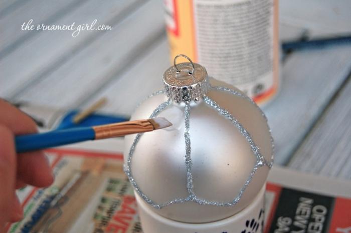 como hacer bolas de navidad, pasos fáciles para decorar un adorno navideño, poner pegamento blanco sobre la bola
