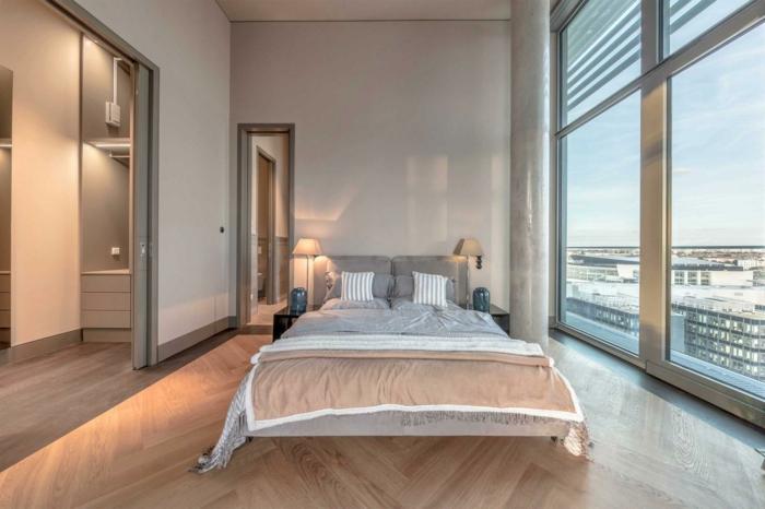 colores para habitaciones, dormitorio luminoso con grandes ventanales, suelo de parquet y decoración minimalista