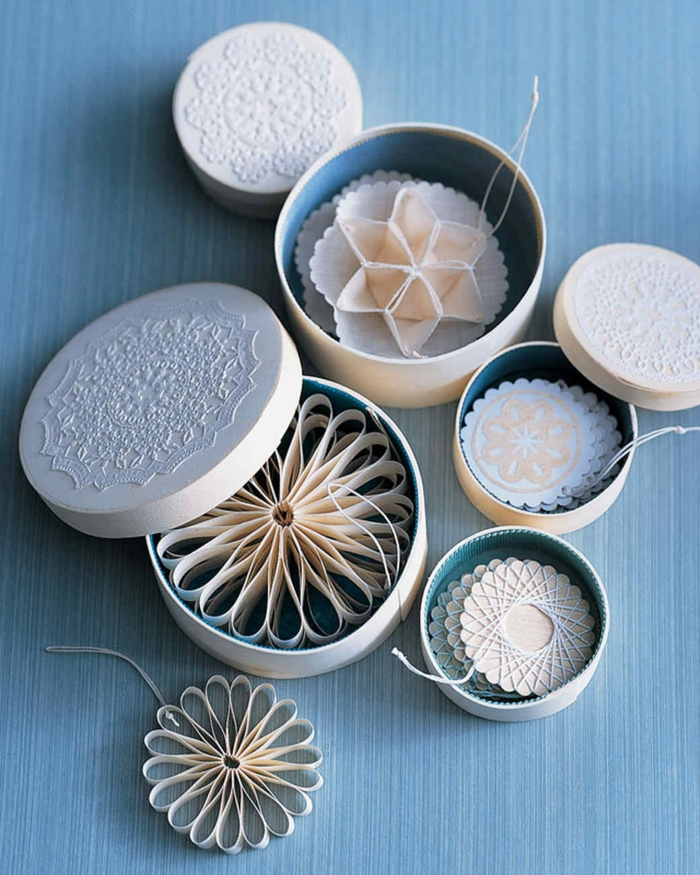 como hacer estrellas de papel, adornos delicados de papel y hilo blanco en forma de estrellas y copos de nieve, cajas de cartón ovales con encaje blanco