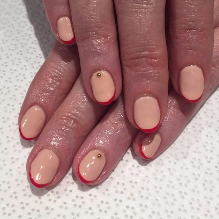 diseño de uñas, uñas preciosas en beige con manicura francesa en rojo y pequeños adornos en dorado, uñas de longitud media en forma redonda