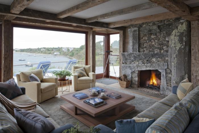 chimeneas de leña, salón encantador en tonos pastel y grandes ventanales, chimenea antigua de piedra, mesa cuadrada de madera