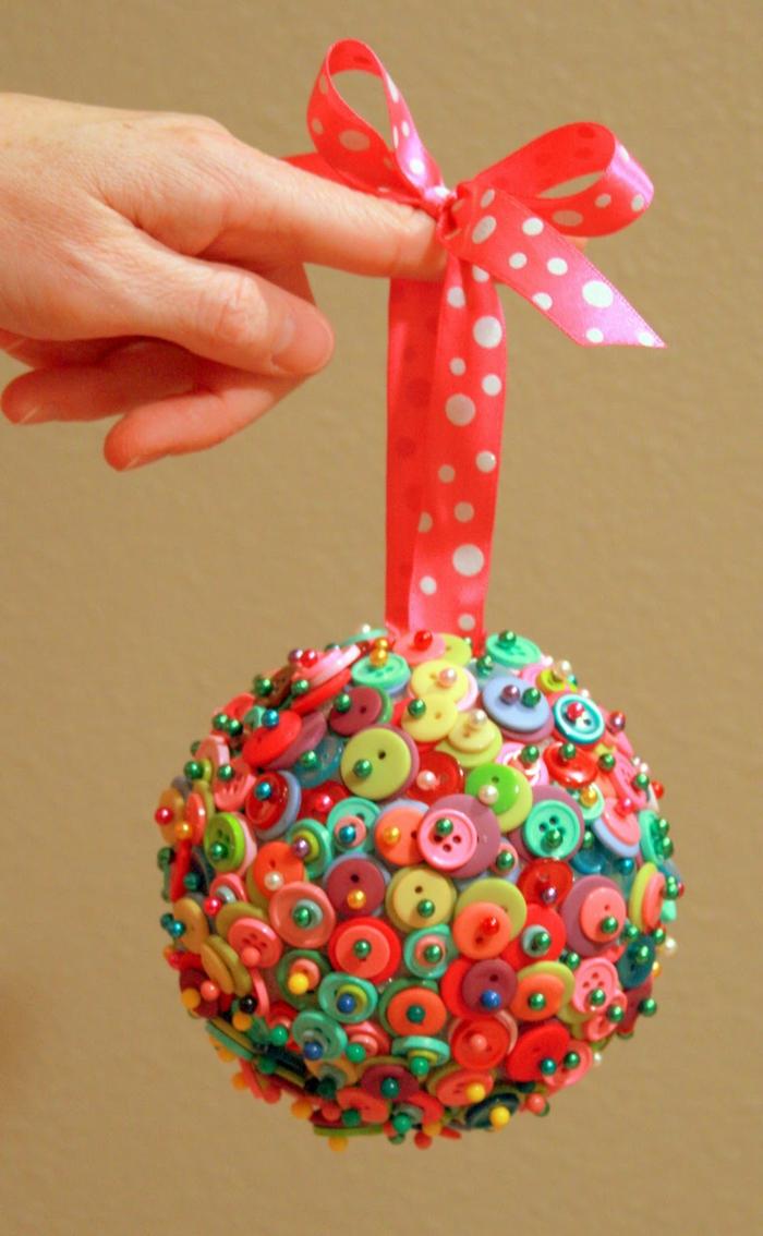 bola navidad, propuesta multicolor casera hecha de bonotes de diferente tamaño y color, cinta roja con lunares en blanco