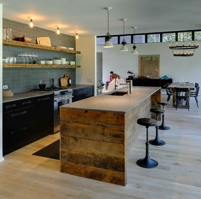 cocinas americanas, cocina con barra de madera y encimera en gris, paredes con azulejos en azul grisáceo, suelo de parquet y sillas de barra negras