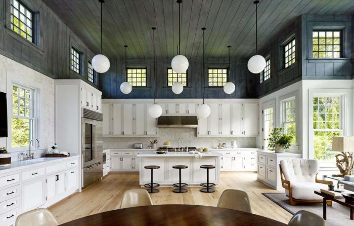 cocinas americanas, espacioso ejemplo en blanco y negro, techo de vigas de madera, suelo de parquet en color claro, muebles en blanco, barra con tres sillas de metal