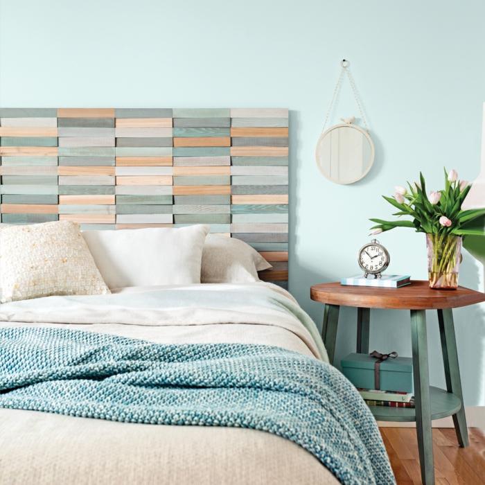 cabecero cama, dormitorio en los tonos pasteles del azul, mesa oval de madera, lecho matrimonio y cabecero original de pequeñas vigas de madera