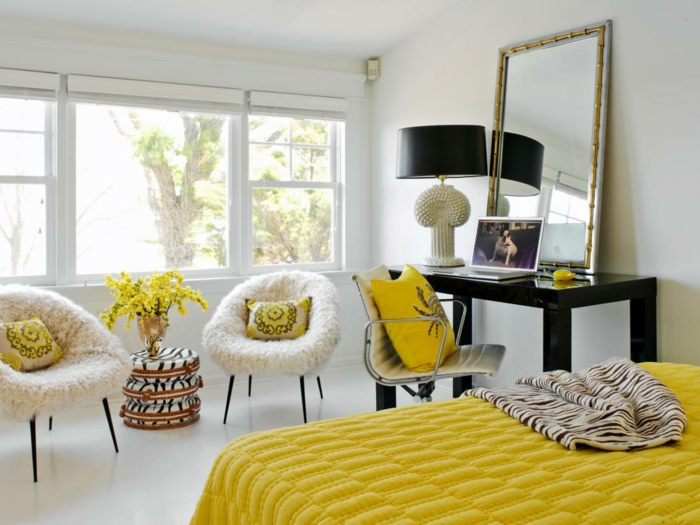 colores cálidos, habitación grande y luminosa en blanco con mucha decoración en amarillo, cojines y cobijas en color mostaza, grande espejo vintage