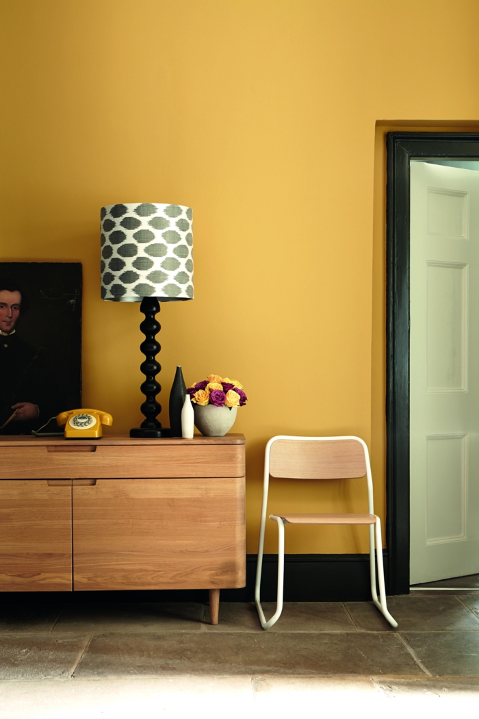 colores calidos, pared en color amarillo mostaza con detalles en negro, armario de madera, teléfono retro, cuadro clásico y decoración de flores