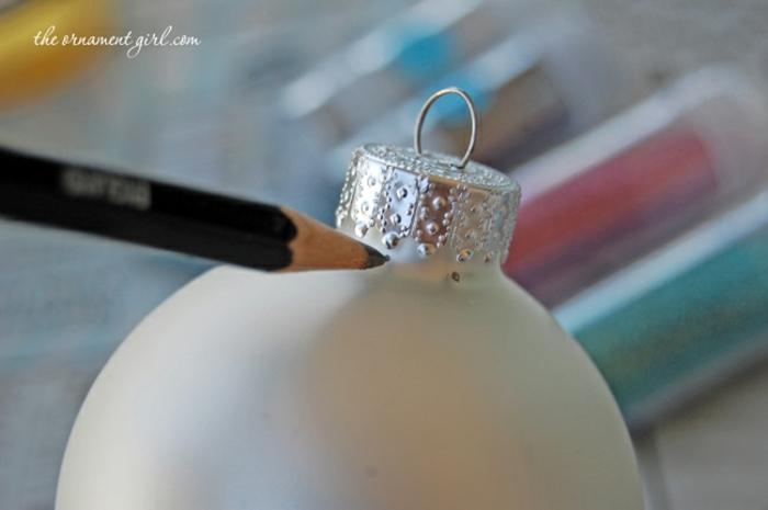 bolas de colores, como decorar un ornamento navideño con purpurina paso a paso, marcar las líneas con un lápiz