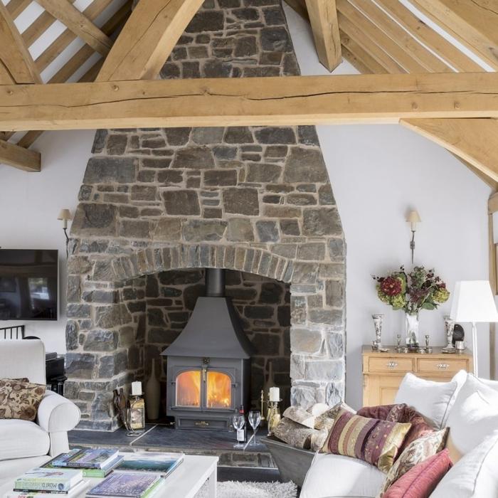 estufas de leña, idea en estilo rústico,grande chimenea de piedra que llega hasta el techo, vigas de madera masivas