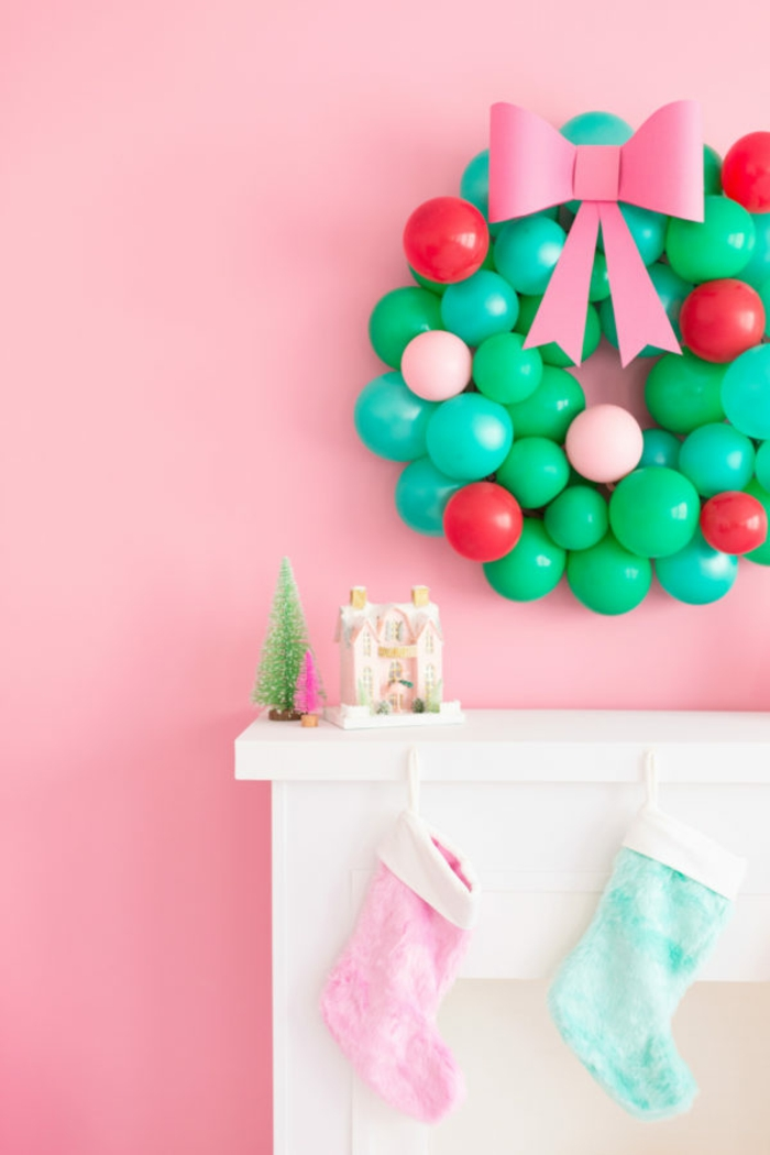 manualidades sencillas, grande corona de navidad para adornar la pared hecha de pequeños globos en verde. rojo y rosado