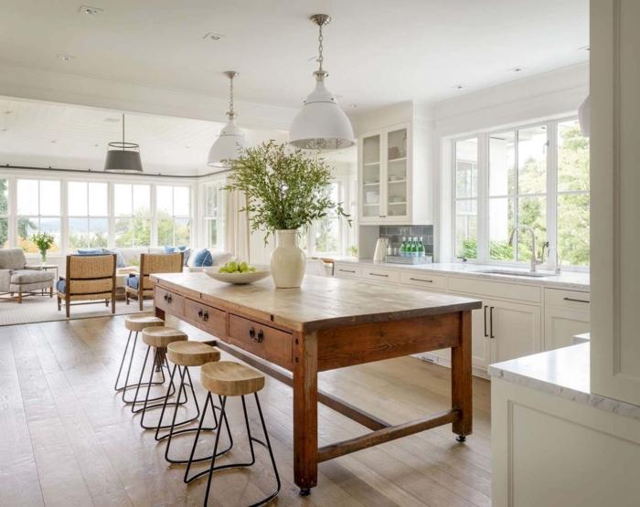 cocinas americanas, cocina espaciosa en blanco con grande mesa de madera en ruedas, sillas modernas de madera y patas de hierro