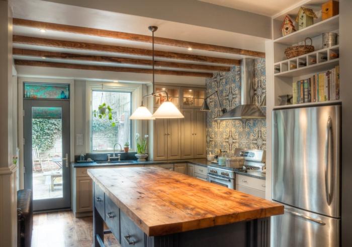 cocinas americanas, cocina en estilo industrial con techo con vigas de madera y barra grande con encimera de madera