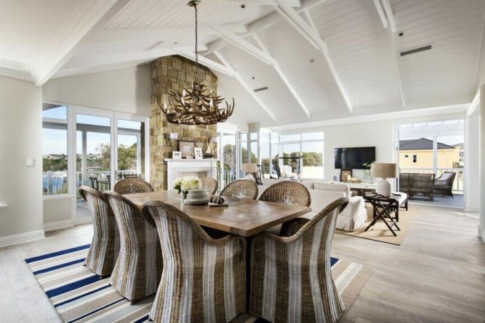 muebles de comedor, araña de madera en estilo rústico, sillas tapizadas, motivos en rayas, techo inclinado y paredes blancas
